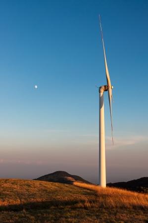 rotates: Wind turbine shovel against blue sky and moon Stock Photo