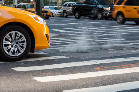 Taxis in Manhattan stopped at traffic lights in front of a manhole