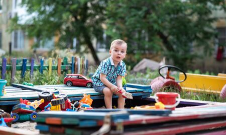 A child plays in the playground with toys in the sandbox. Toddler boy plays in the sand in the summer. Cheerful children's vacation outside.