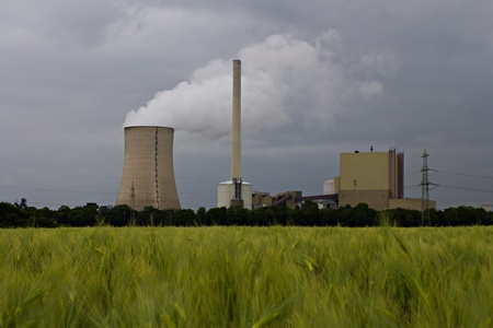The picture shows a power plant and a grainfield. photo