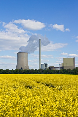 utilities: Rape field and power plant under a blue sky. Stock Photo