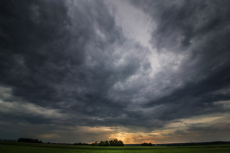 storm damage: The picture shows a storm that?s brewing over a field. Stock Photo