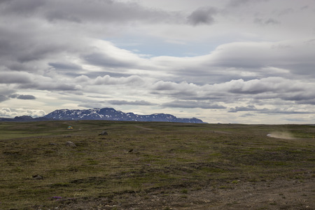 ber: Das Bild zeigt eine Berglandschaft auf Island, in der ein Auto über eine Schotterpiste fährt. Stock Photo