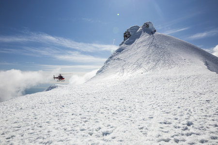 helicopter: The picture shows the snow-capped peak of a mountain, on which a helicopter is landing and a closer look reveals two climbers.