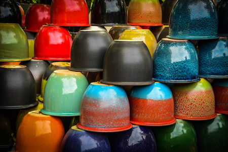 Stacks of colorful ceramic and porcelain tree pots. Local ceramic pots and designs factory outlet, Kanchanaburi, Thailand.  Thailand Ceramic products factory outlet Фото со стока