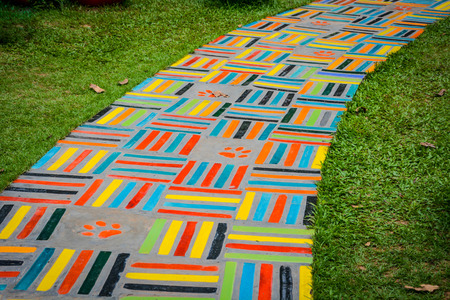 The colorful ceramic walking path on green grass field. Fun and lively walkway.