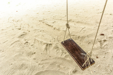 Empty wooden rope swing hang isolated above a white sand beach.
