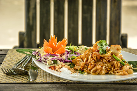 Padthai, Thai traditional stirred fried noodle with egg and prawn. Famous Thai dish.  Padthai serves with seasoning aside and decorations on the table with a set of fork and knife.