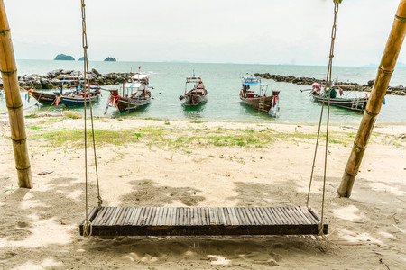 The relaxing outdoor bamboo swing with beach view and boats, Thailand Фото со стока
