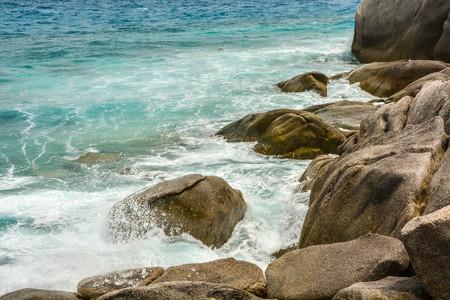 Turquoise Seawater splashes on rocky shorelines background