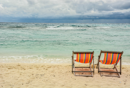 Two beach chairs on white sand beach face with turquoise green sea and cloudy sky. Relaxing on beach icon. Holiday icon. Summer holiday background.