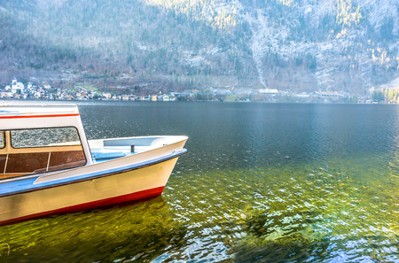A yellow ferry boat floating on clear lake Hallstatt with alpine background