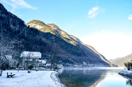 Nice clear sky and Winter nature landscape of village by the Lake Hallstatt covered by snow and water reflection. Фото со стока