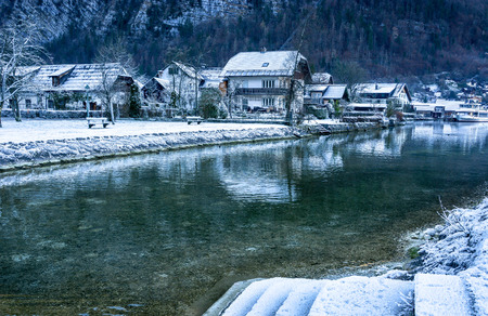 Winter landscape of snow covered houses by the Lake Hallstatt, Austria
