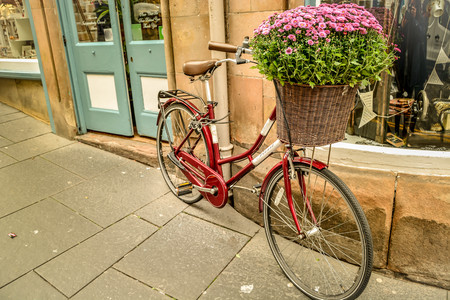 Red Bicycle with full of flowers in the front basket park isolated in front of old building facade