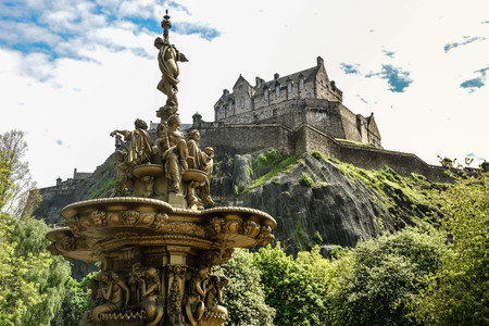 A view of Edinburgh Castle and fountain from the Princes Street gardens public park, Edinburgh, Scotland, United Kingdom