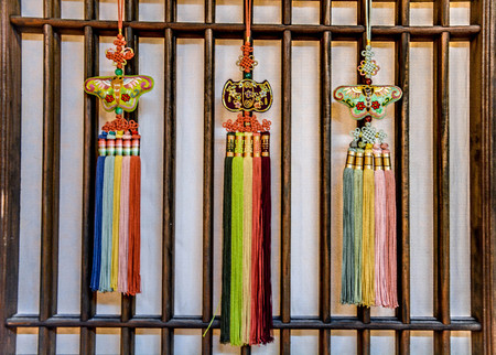 Hanging Korean traditional handicraft knots on paper wooden wall background Фото со стока