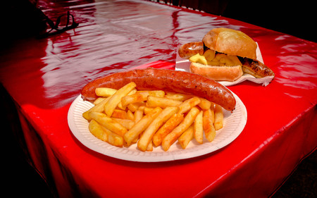 German Sausage and fries serves on paper dish with red table background Фото со стока