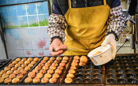 Making Takoyaki, a ball-shaped Japanese snack made of a wheat flour-based batter and cooked in a special molded pan. Japanese street food stall. Banque d'images - 102674029