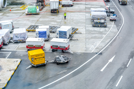 Airport shipping cargo boxes and trucks on runway Banque d'images - 129999944