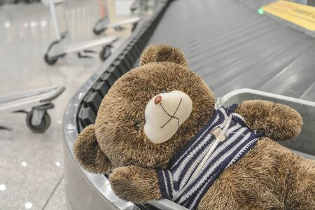 Cute brown teddy bear has been sadly abandoned alone on the moving baggage belt at the airport Banque d'images - 133874443