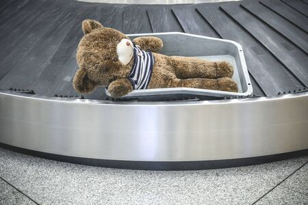 Cute brown teddy bear has been sadly abandoned alone on the moving baggage belt at the airport Banque d'images - 133874448