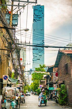 Skyscraper among local slum background. Wealth and Poverty background of Bangkok Metropolis, Thailand, May 2020 Stock Photo