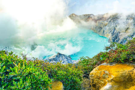 Emerald green sulfur acid lake and toxic gas at the bottom of active volcano crater, Kawah Ijen, East Java, Indonesia