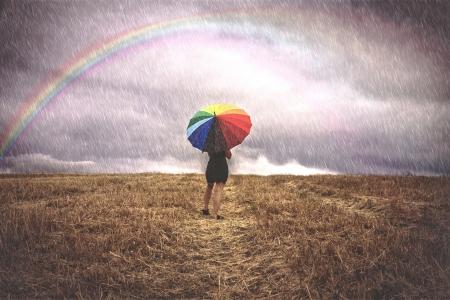 Vrouw op gebied met kleurrijke paraplu in de regen