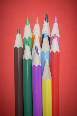 Colored pencils on red background photo