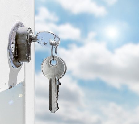 Keys in a lock with sky background photo