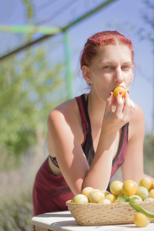 Young woman biting a plum photo