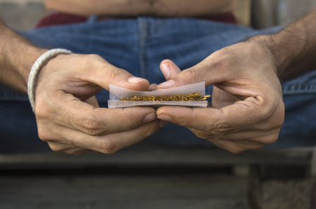 Close-up photograph of a mans hands rolling a joint