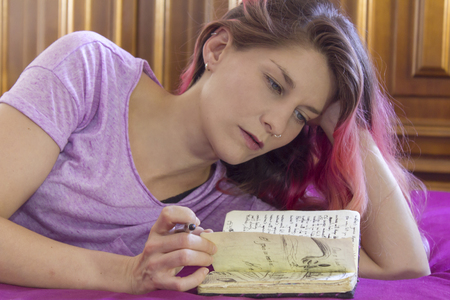 Young woman reading a notebook in bed