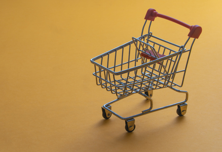 Shopping cart on yellow background