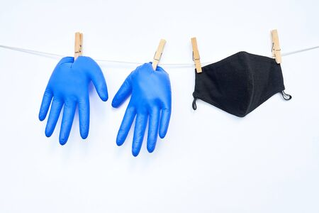 Blue medical gloves and black reusable fabric mask hang on cord, attached with pins.