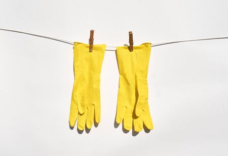 Yellow household gloves hang on cord, attached with pins.