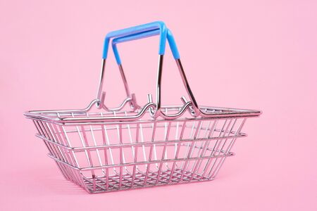 Side view of supermarket shopping basket on pink background. Black friday sale concept. Copy space. Sustainable lifestyle