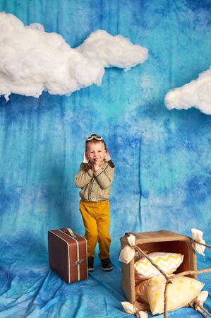 Dreams of travel. Funny child flying on the sky with clouds