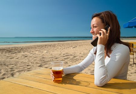 Girl sitting&talking by phone on a beach