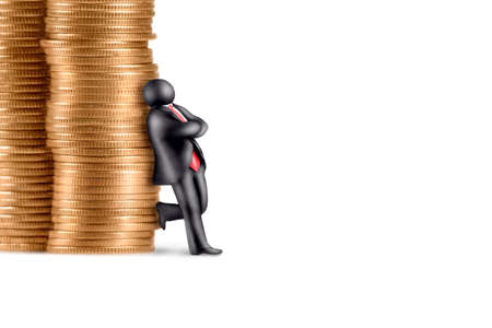 Plasticine figure of cross-armed businessman leaning against the stacks of coins