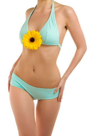 A fragment of woman  body in blue panties and yellow gerbera
