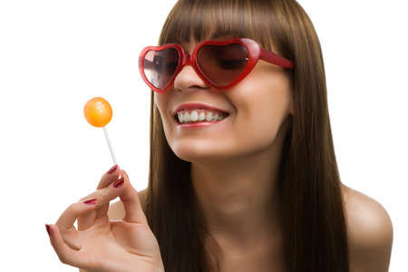 A woman sucking a lollipop on a white background Stock Photo - 13570002