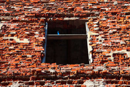 Window and brick wall of a ruined house photo