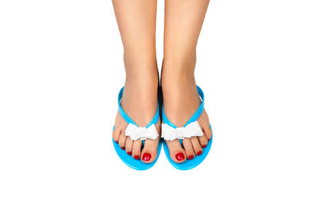Female foot with pedicure in blue slippers on a white background photo