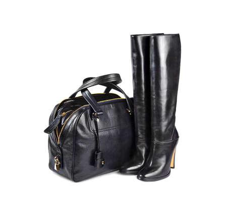 leren tas: Zwarte vrouwelijke tas & laarzen op een witte achtergrond. Stockfoto