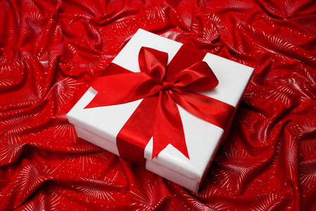 White gift box with red bow and ribbon on red background photo