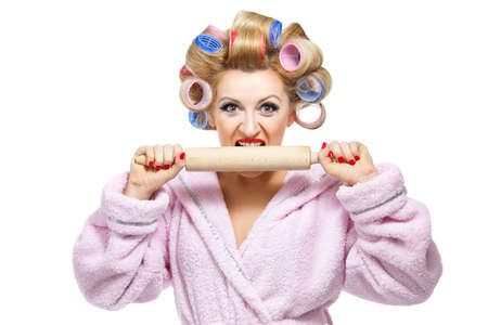 Housewife in pink bathrobe biting rolling pin on white background Stock Photo - 17534950