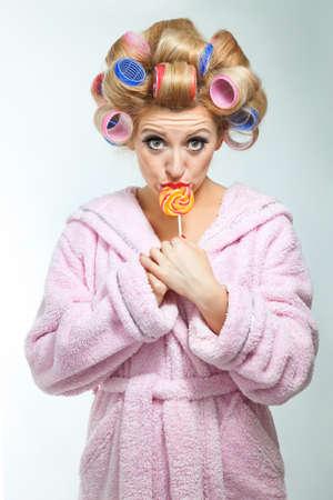 Hausfrau in rosa Bademantel mit lollypop Standard-Bild