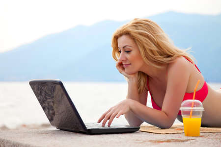 Attractive blond woman on a seacoast with notebook photo